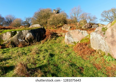 Trees and fallen rocks lay around the Derbyshire rock formation called Robin Hoods Stride.