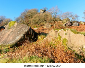 Trees and fallen rocks suround the Derbyshire rock formation called Robin Hoods Stride.