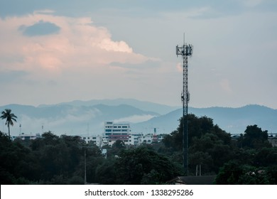 Trees in front of the building ,clound sky ,fog and mountain background.