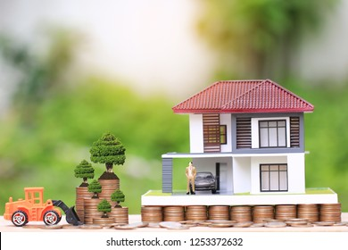 Trees growing on coins money and Truck toy with businessman standing on model house and car on natural green background,Saving plans for housing,Repair maintenance,investment and business concept
