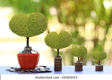 Trees growing on pile of coins money in flowerpots on green background, investment and business concept
