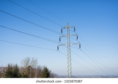 Trees. High voltage columns, in the background with blue sky and clouds. Prices of electricity, consumption, ecology.