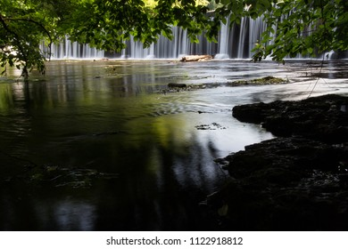 Trees leaning over a river with a waterfall in the background.  Old Stone Fort State Archaeological Park, Manchester, TN, USA.