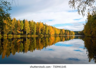 Trees reflected in the blue lake . Autumn landscape