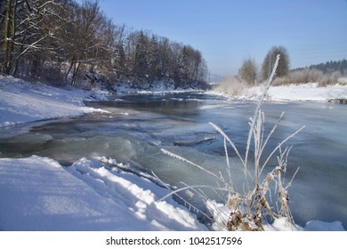 Trees, shrubs, snow and ice line the Becva River in a gentle bay