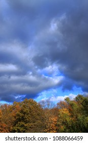 Trees and Storm Clouds Background - Heavy dark clouds over a forest with the colors of autumn.
