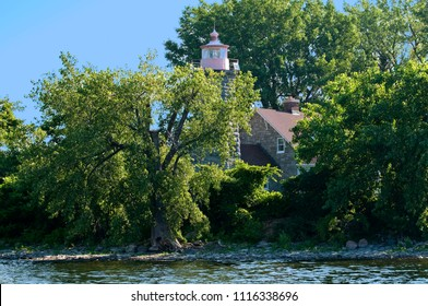 Trees surround historic Windmill Point lighthouse, with it's stone construction. It is the most northern beacon in Vermont on Lake Champlain.