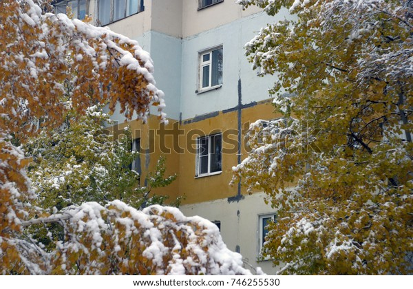 Trees with yellow, green, orange, red leaves are covered with white and pure snow, against the background of a yellow, blue house with windows. The first snow in the fall. Autumn and winter background