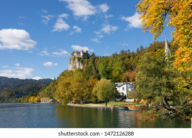 Trees in yellow and orange autumn colors foliage at the shore of Lake Bled with tourist boats in the water and Bled Castle on a cliff high above the lake on a beautiful fall day in Bled, Slovenia.
