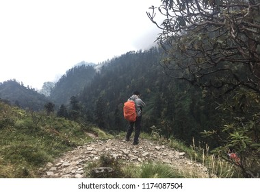 A trekker with backpack walking on trail of Annapurna Circuit Trekking in Khopra, Nepal.