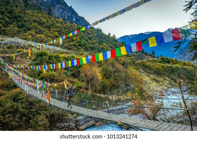 Trekker crossing metal suspension bridge in Nepal, Himalayas, Manaslu circuit trek 2017