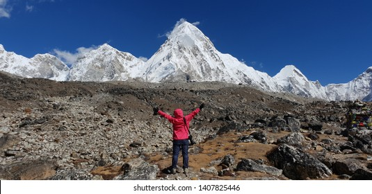 Trekker hand up two hands with Pumori mt. and Kala patthar view from Gorak shep village in background in Everest Base Camp,Nepal.