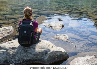Trekker sitting on a big rock on the shore of a very clear water
