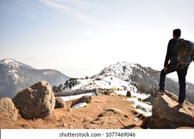 Trekker soaking in the views of Dhuladhar from atop Triund hilltop