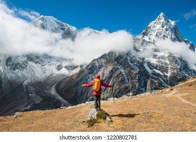 Trekker standing in front of Mt.Taboche (6,501 m) at the left side and Mt.Cholatse (6,440 m) at the right side during trekking from Lobuche to Dzongla village in Nepal.