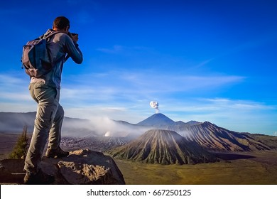 Trekker taking photo of Gunung Bromo volcano in Java, Indonesia