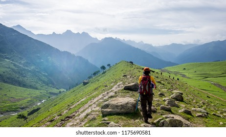 A trekker walks past Gadsar lake and a meadow at kashmir great lakes trek in kashmir. Solo person in the mountains and lake of Kashmir, India. The breathtaking view of Krishansar lake on blue sky.