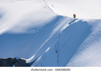 Trekkers hiking up a snowy ridge on White Valley, Mont Blanc massif from Aiguille du Midi 3842m, Chamonix, France