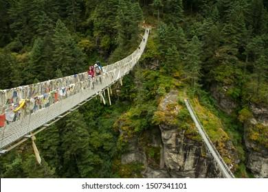 Trekkers and Sherpa crossing a suspension bridge in Everest base camp route at (Sagarmatha National Park - Himalaya), Nepal.