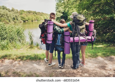 Trekking, camping, harmony, peace concept. Rear view of two couples of friends bonding on the bench of the lake, looking at the beautiful view, enjoy and relax
