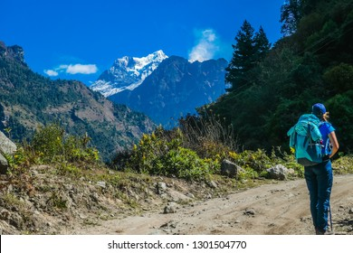 Trekking girl with a big blue backpack admires Manaslu, Annapurna Circuit Trek, Nepal. Forest to the right. To the left another Mountain. Manaslu covered with snow. Flowers next to the trekking trail.
