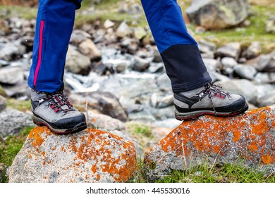 trekking and hiking boots walking on the orange lichen covered stones. Concept of quality shoes