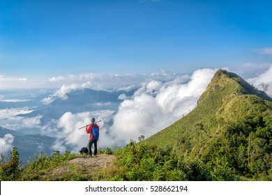 Trekking man is excited with the mist on the top of the mountain at  Phu Chee Dao, Chiangrai Thailand