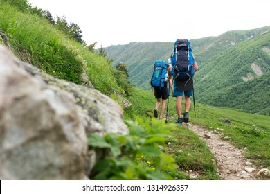 Trekking in mountains. Climbers with backpacks hiking in mountain trail. Tourists hike to summit