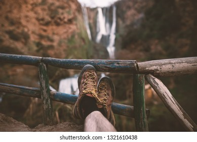 Man´s trekking shoes in a nature of Morocco - Ouzod falls. Close up of hiking boots against waterfall. Man hiking enjoying a view after trek.