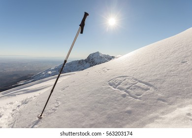 Trekking stick and traces of snowshoes in high mountains. Italian Alps.