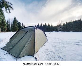 Trekking tent built  against the snowy landscape. Winter skialpinism trek over snowy mountain peaks.
