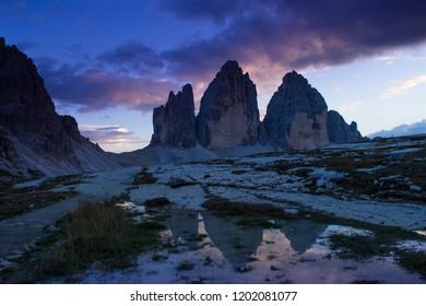 trekking at tre cime di lavaredo, dramatic sunset, dolomites in italy