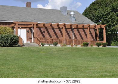 a trellised covered handicap ramp by a red brick building