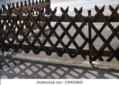 trellis-work fence at courtyard entrance casting shadow on tarmac on sunny day