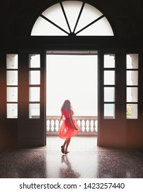 Tremezzina, Italy - June 24, 2017: A twirling girl on the main door at Villa Carlotta in Tremezzo on Lake Como with a red dress