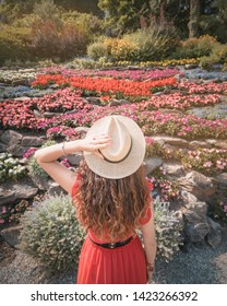 Tremezzina, Italy - June 24, 2017: A girl with a straw hat in front of botanical garden's flowers at Villa Carlotta on Lake Como