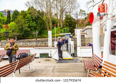 Tremezzo, Italy - 15 April 2018 - Unidentified tourists step away from and aboard to while the Ferry stopping at Villa Carlotta port (Scalo di Villa Carlotta).