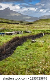 Trench cut into deep Peat of wetland moors near Drinan on Isle of Skye Scotland with Loch Slap and Beinn Na Caillich mountain peak
