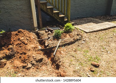 Trench dug in preparation to install a drainage system for a house gutter downspout