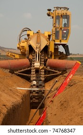 Trencher machine in sandy ditch on pipeline construction site