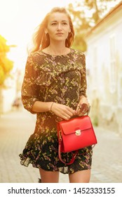 TRENCIN, SLOVAKIA - JUNE 16, 2019: Young european caucasian woman on the street in modern clothes and with current red leather purse bag. Young girl with handbag walking on the street in sunlight.