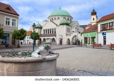 """TRENCIN, SLOVAKIA - MAY 16, 2019: Sturovo square with """"Vodnik Valentin"""", famous touristical attraction. Jewish Synagogue in the background. Kelpie Valentin in Trencin. Slovak Republic, Central Europe."""