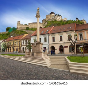 TRENCIN, SLOVAKIA - MAY 18, 2019: Plague Pillar (Morový stĺp) in the city center. Plague monument placed on main square. Trenčín Castle in the background. Trencin, Western Slovakia, Central Europe.