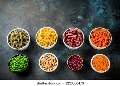Trend healthy food, vegan diet concept. Multi colored legume pasta with raw beans. Beans, chickpeas, green peas, lentils. Copy space top view