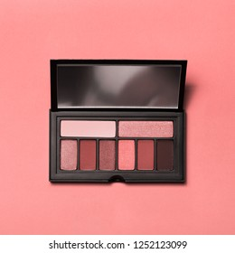 Trend photography on the theme of the new color of the year 2019 - Living Coral. Palette of living coral eyeshadows from high view