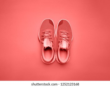 Trend photography on the theme of the new color of the year 2019 - Living Coral. Pair of living coral sport shoes on background
