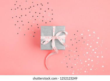 Trend photography on the theme of the new color of the year 2019 - Living Coral. Christmas gift with  living coral ribbon on living coral pastel background with festive decorations.