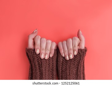 Trend photography on the theme of the new color of the year 2019 - Living Coral. Closeup of hands of a young woman with winter snowflake manicure of New trending Living Coral color