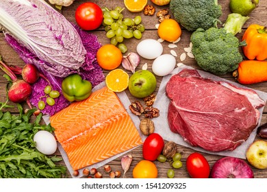 Trending paleo/pegan diet. Healthy balanced food concept. Set of fresh products, raw meat, salmon, vegetables and fruits. Old wooden boards background, top view