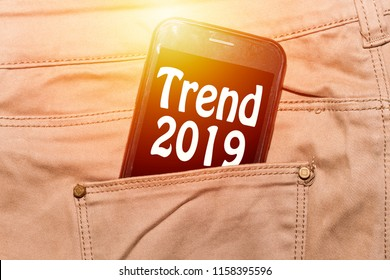 Trends 2019 inscription on phone screen / Smartphone in front pant pocket